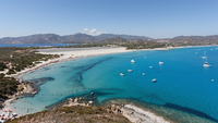 Blue bay with boats and mountains on horizon, Sardinia, Italy