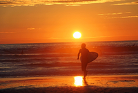 Silhouette of surfer at sunset, France