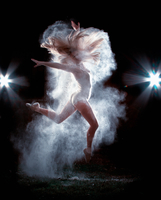 Young woman jumping in air in dust cloud in front of black background and lights, Northwest Arkansas 11098020584| 写真素材・ストックフォト・画像・イラスト素材|アマナイメージズ