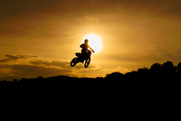 Motocross rider silhouette in mid-air at sunset, Corigliano Calabro, Calabria, Italy