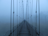 Man cycling on suspension bridge, Khokana, Bagmati Zone, Nepal