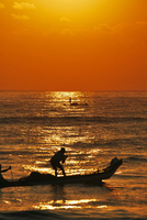 Silhouettes of fishermen on boats at sunset