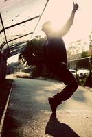 Man dancing on city street, Orange County, California, USA
