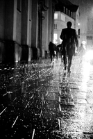Silhouette of man walking on pavement in rain, Munich, Germany