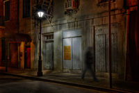 Man walking on sidewalk at night, French Quarter, New Orleans, USA