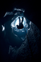 Man rappelling down in ice cave, Norway