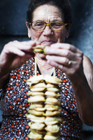 Senior woman putting food on skewers, Calabria, Italy