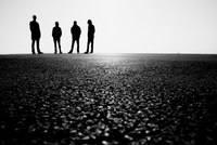 Silhouettes of four men standing on asphalt, Barcelona, Catalonia, Spain