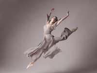 Studio shot of ballet dancer dancing on grey background