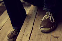 Man's feet in old sneakers on wooden porch