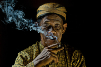 Man wearing traditional clothing with cigarette, Jitra, Kedah, Malaysia