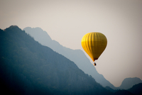 Yellow balloon floating over mountains, Laos