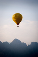 Yellow hot air balloon floating over mountain tops, Laos