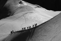Explorers on edge of mountain, Aiguille du Midi, Mont Blanc, French Alps, France