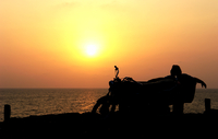 Motorcyclist sitting on a bench by the sea at sunset, Goa, India