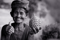 Smiling elderly woman holding fruit, Bali, Indonesia