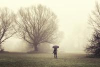 Woman with umbrella looking at fog, Kiskoros, Bacs-Kiskun county, Hungary