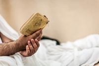 Mid adult man reading Koran, Mina, Saudi Arabia