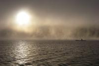 Man canoeing through Windermere lake in English Lake District, Cumbria, England, UK
