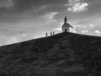 Three people walking to church on top of hill, The Hague, Leidschenveen, The Netherlands