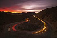 Car lights along mountain road at night, Los Angeles, California, USA