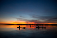 Silhouette of fishermen at sunset on Amazon River, Iquitos, Peru