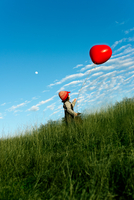 Boy (6-7) with red balloon on meadow