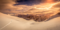 Man skiing in mountains at sunset, Alpes, France