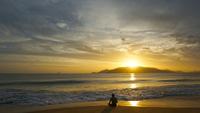 Man sitting on seashore at sunrise, Nha Trang, Vietnam
