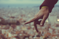 Male hand with extended index finger against cityscape, Barcelona, Spain