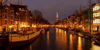 Illuminated Amsterdam canal at dusk, Amsterdam, Netherlands
