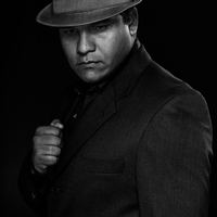Portrait of man in suit and fedora against black background