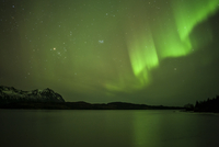 Green aurora borealis over lake