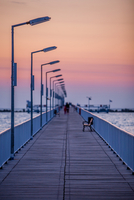 People walking on bridge at sunset, Constanta, Romania
