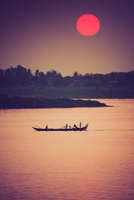 Silhouette of fishing boats with people in Mekong river at sunrise, Cambodia