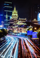 Traffic light trails and illuminated temple, Shanghai, China