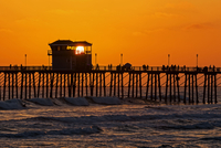 Silhouettes of people standing on pier at sunset, Oceanside, California, USA