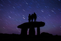 Silhouette of three people standing on Lanyon quoit and stargazing, Cornwall, England, UK