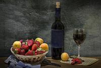 Fruits in wicker basket and bottle of wine