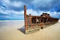Rusty shipwreck of SS Maheno on sandy beach under cloudy sky, Fraser Island, Australia