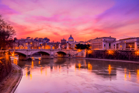 Ancient Roman arch bridge Ponte Sant Angelo over Tiber river and old town at sunset, Rome, Italy