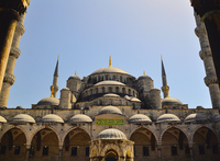 Domes of Sultan Ahmed Mosque viewed from courtyard under clear sky, Istanbul, Turkey