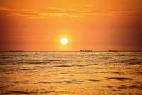 Sun over Baltic Sea at orange color sunset with ships on horizon, Latvia