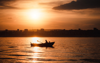 Silhouette of man in boat on Volga at sunset, Saratov, Russia