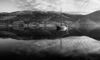 Reflection of mountains and boat on lake, Scotland, UK