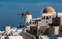 White buildings and Greek flag under blue sky, Santorini, South Aegean, Greece