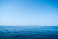 Sparse seascape of calm Aegean Sea with lone sailboat under clear sky, Greece
