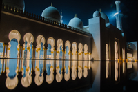Arches of Sheikh Zayed Mosque entrance exterior reflecting in pool at night, Abu Dhabi, United Arab Emirates