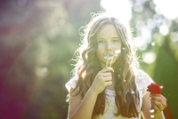 Teenage girl (13-15) blowing off dandelion seeds and holding red rose