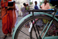 Close-up of back wheel of bicycle and buddhist monk in background, India